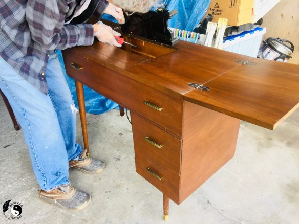 hand removing metal pieces from sewing table for how to get smell out of old furniture
