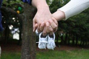 Baby shoes held by couple holding hands