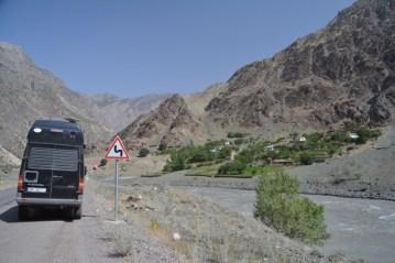 Pamir highway with an Afghan village on the right/La route de Pamir avec un village afghan à droite