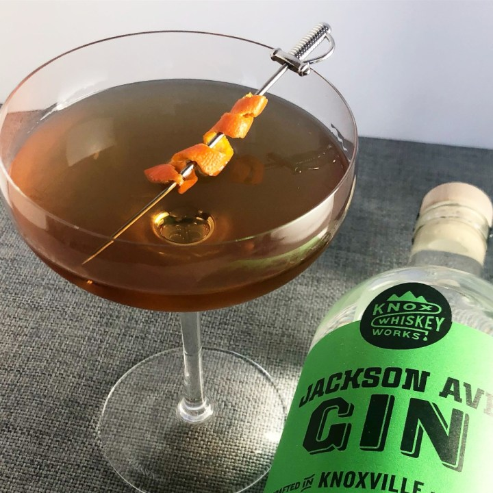 Photo of the Martinez Cocktail in a coupe glass next to a bottle of Jackson Avenue gin with a green label.