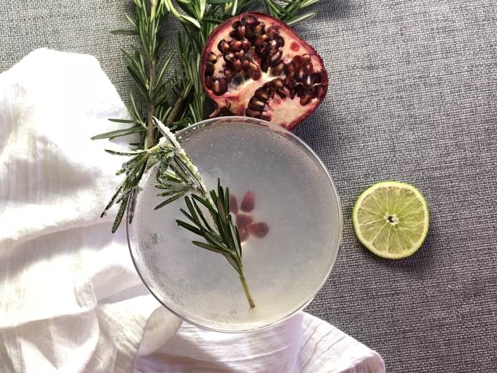Top down view of a gin gimlet, garnished with rosemary and pomegranate arils. Surrounded by a white tea towel, a lime wheel, a half of a pomegranate, and extra rosemary.