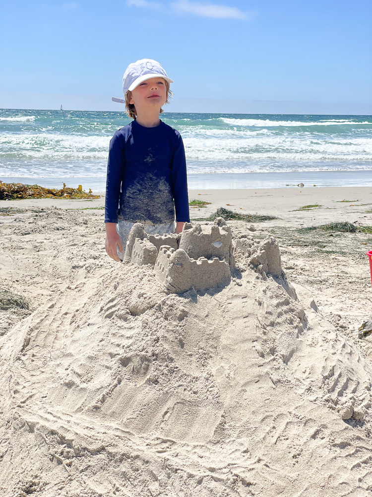 little boy with white hat and sand castle at the beach