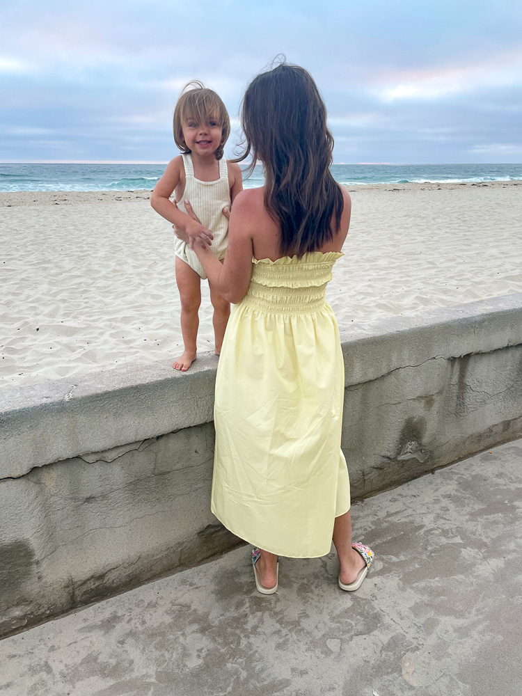 mom with toddler standing at sea wall