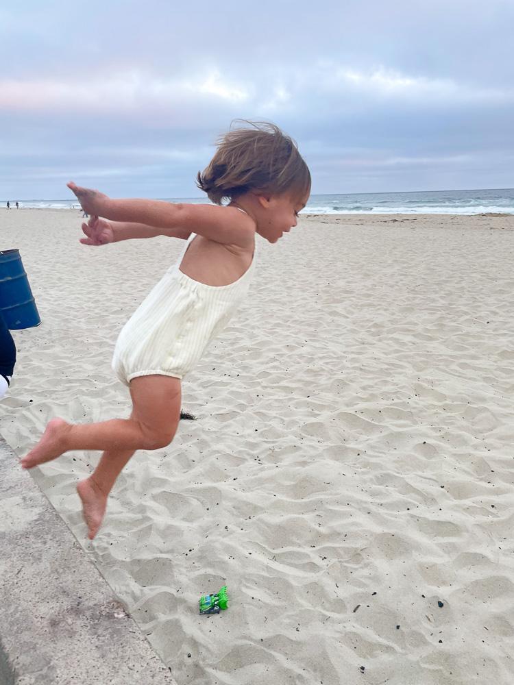 toddler jumping at the beach