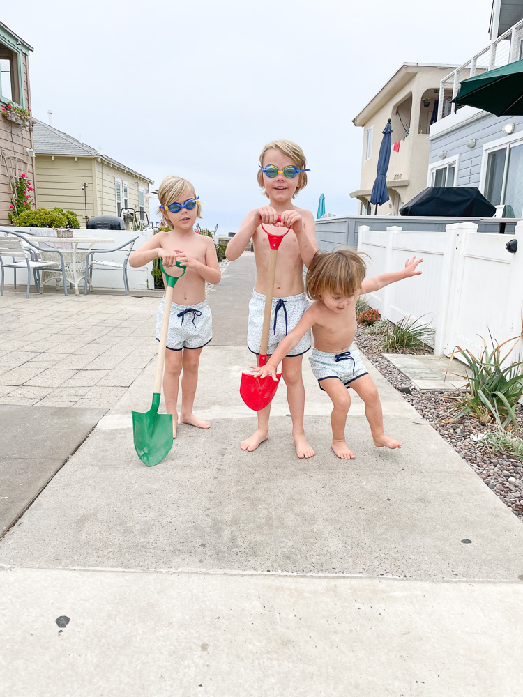 three little boys in swim trunks and goggles