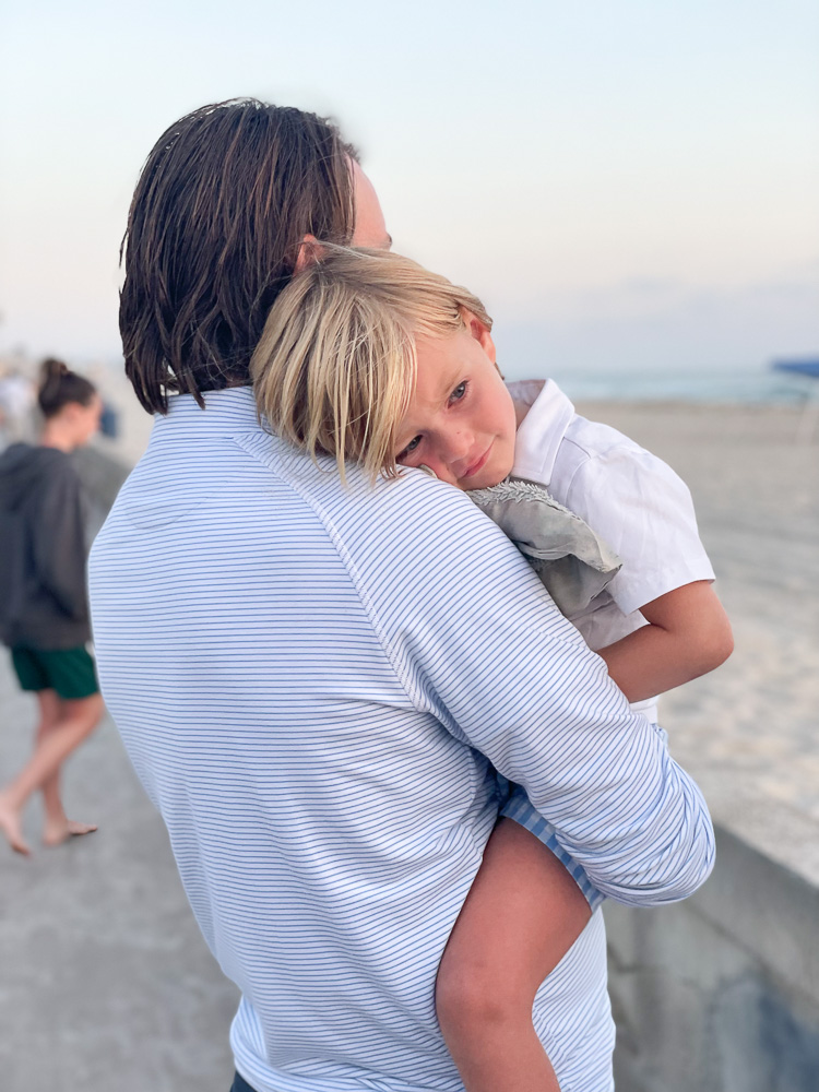little boy resting head on dads shoulder