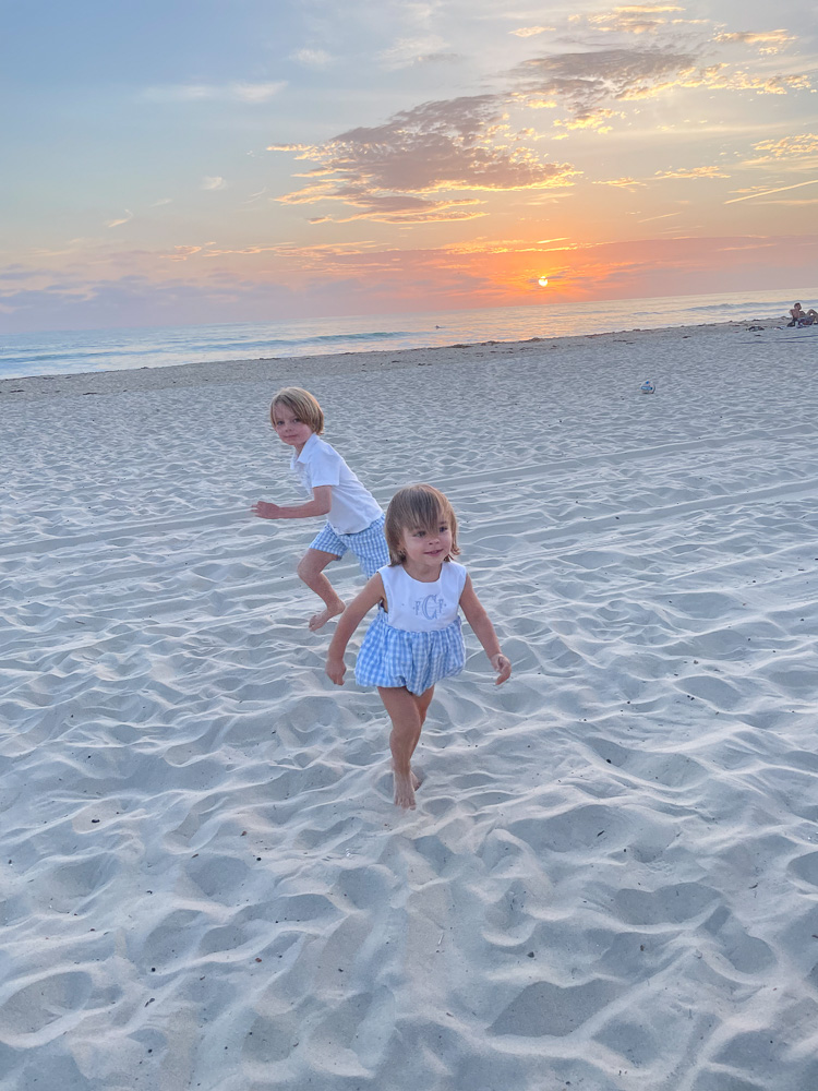 two little boys playing in the sand at sunset