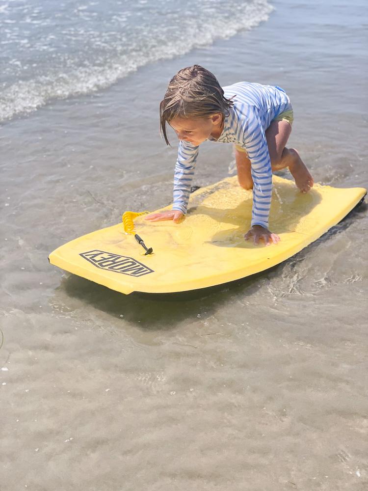 little boy riding boogie board at the beach