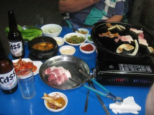 Samgyeopsal (pork belly meat - looks like bacon), a lot of kimchies, a spicy soup, onion and fresh salad.