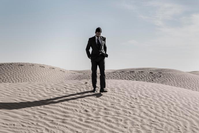 a man in a suit walks over a sand dune