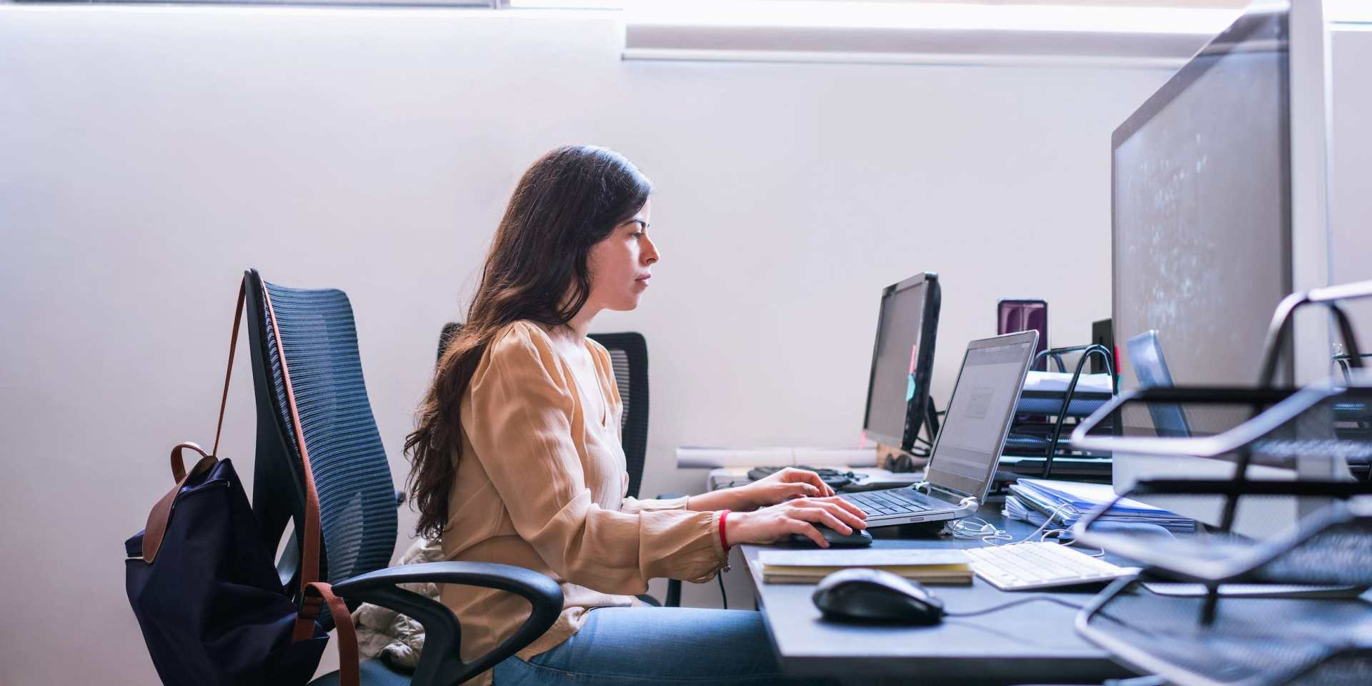 business professional working on laptop desktop PC in office