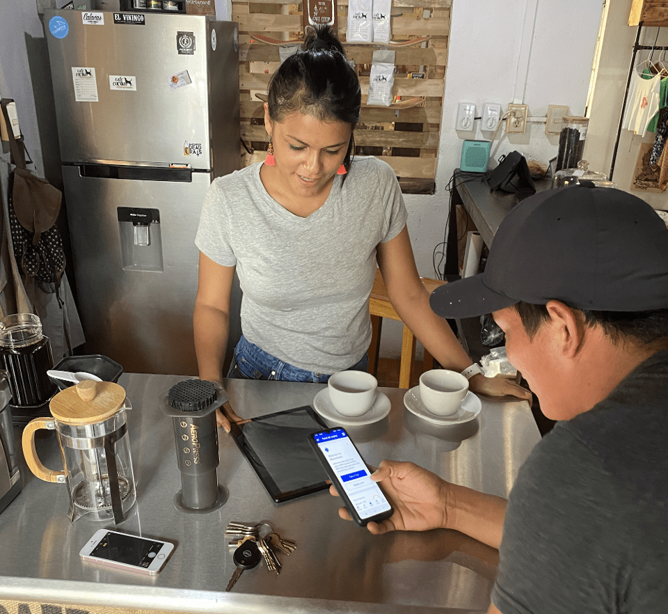 Jorge Valenzuela training a local coffee shop owner to use Bitcoin.