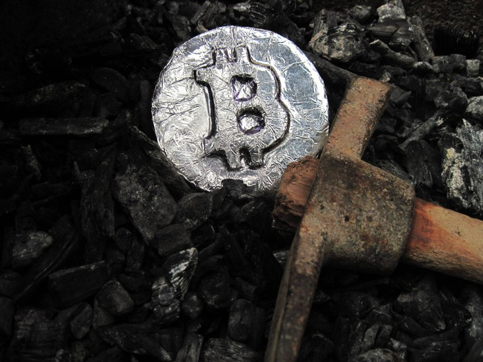 A pick ax sits next to a coin displaying the bitcoin symbol.