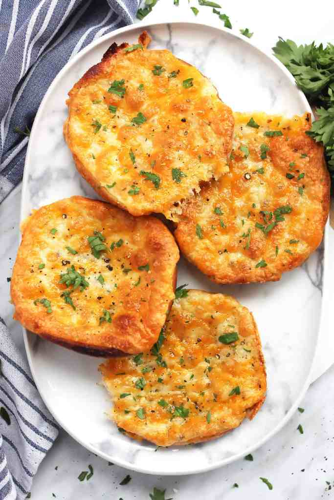 Four slices of cheesy garlic bread on a plate