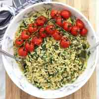 Overhead shot of orzo salad in a bowl topped with roasted tomatoes
