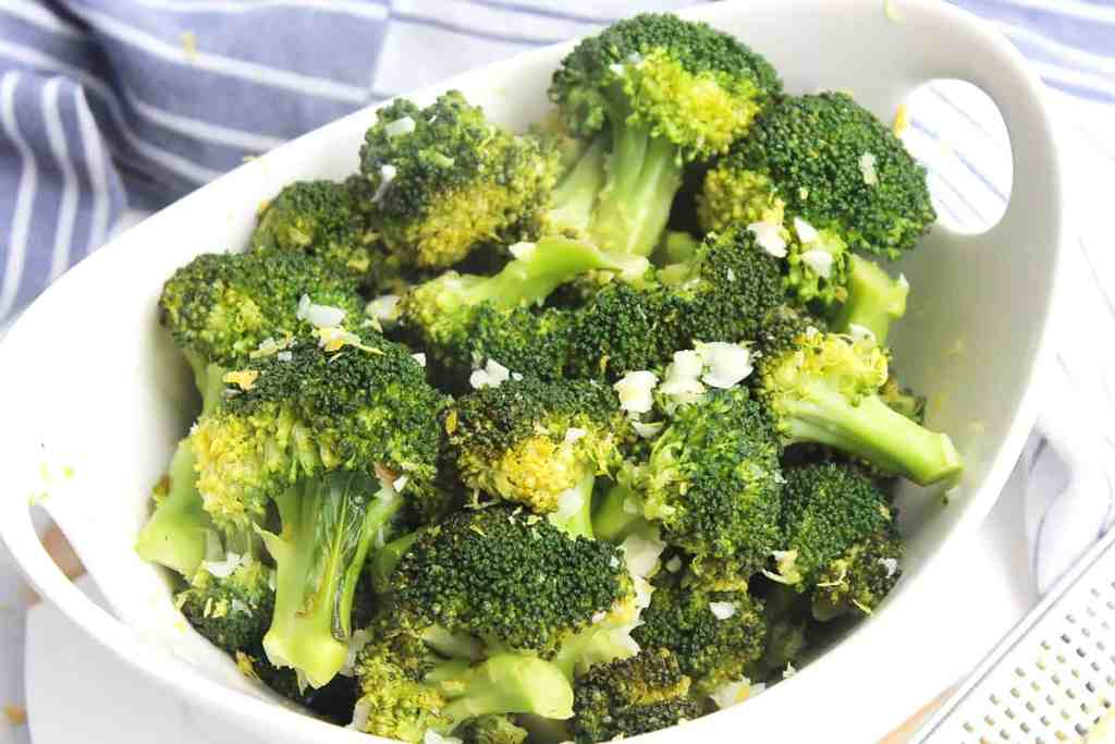 The cooked broccoli in a bowl topped with grated lemon zest.