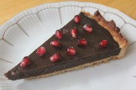 A tart with a sweet shortcrust shell and a creamy chocolate ganache filling garnished with pomegranate seeds.