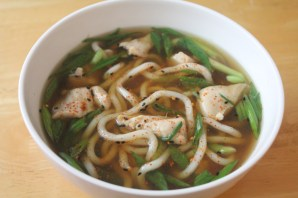 Udon soup with chicken pieces and scallions.