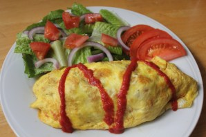 Chicken fried rice with tomato sauce wrapped in an omelette.