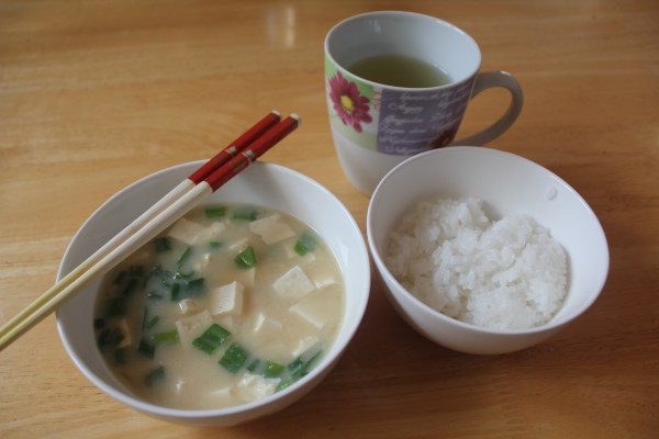 Miso soup with tofu and scallions served with steamed rice.