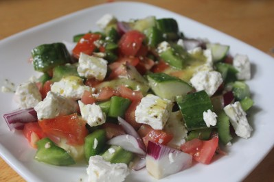 A salad with diced cucumbers, tomatoes, bell peppers, red onions, feta cheese, and drizzled with an olive-oil based dressing.