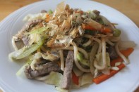 Udon noodles stir-fried with beef slices, bell peppers, carrots, onions, and cabbage.