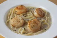 Pan-seared scallops served with linguine pasta in wine sauce.