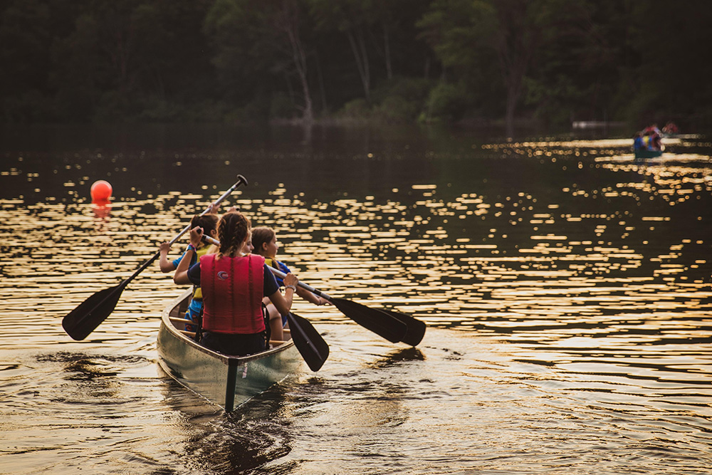kids paddling in a canoe