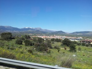 Landscape of Madrid Region.  Green plains with settlements of red roofs and mountains on the horizon