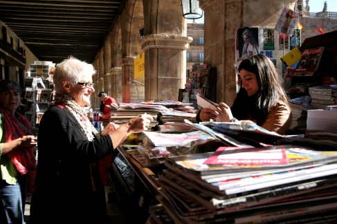 Buying magazines and postcards at a bookstall in Salamanca