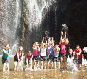 a group of girls playing in the pool at the base of a waterfall