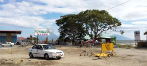 Ferry port, very much a building site, a car in the foreground, signs and cones with barriers. In the background the volcano of Concepcion