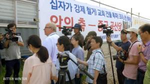 Mr. Zoehrer between demonstrators and journalists