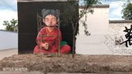 """A mural of a Buddhist nun sitting in meditation has been modified into a """"young girl."""""""