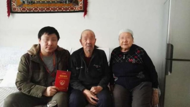 "A Han official's photo with his Uyghur homestay family taken after the signing of ""the homestay card"""