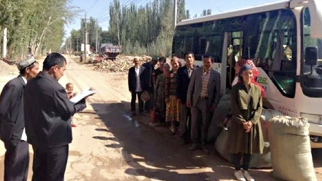 Uyghur workers bused to forced labor.