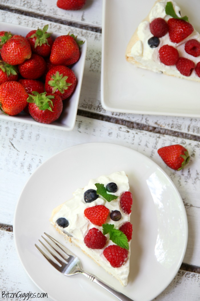 Triple Berry Pavlova - This meringue cake is crisp on the outside and soft and light on the inside! Topped with homemade whipped cream and fresh berries, it's such an elegant, light and delicious dessert!