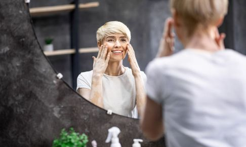 Mature Skincare Routine. Beautiful Middle-Aged Lady Touching Face Perfect Skin, Smiling Looking In Mirror Standing In Bathroom.