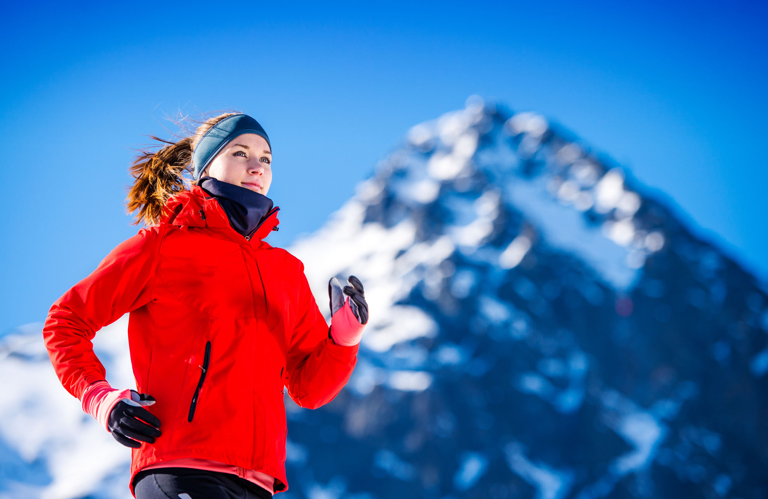 46625131 - young woman jogging outside in sunny winter mountains