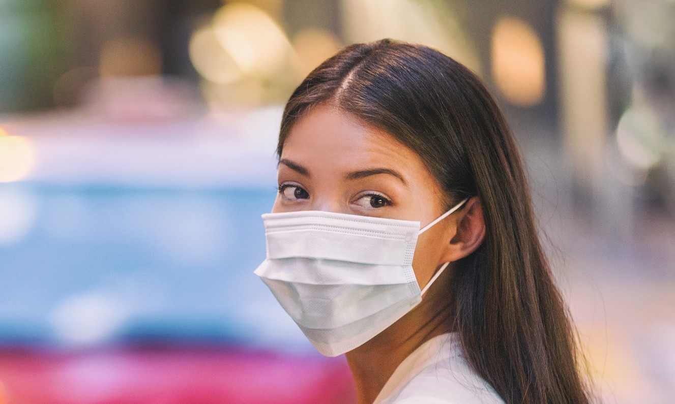 Flu virus protection mask protective against influenza sickness viruses and disease. Sick sian woman wearing surgical face mask in public spaces. Healthcare banner panorama concept.