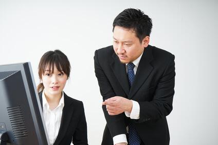 若い女性が男性にパソコンの指導を受けている