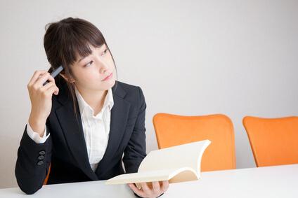 ノートとペンを持って考えている女性