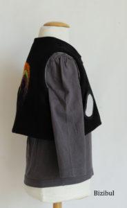 détail du gilet sans manche ; une poche ronde bordée de biais noir est appliqué sur le devant droit du gilet