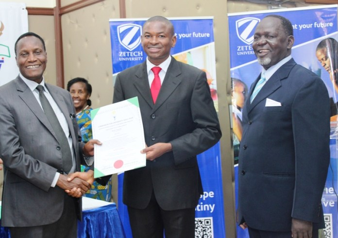 Ken Mbiuki receives university charter from Prof. Jacob Kaimenyi, Cabinet Minister for Education