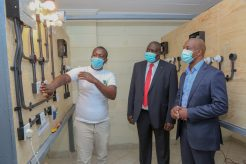 John Ndungu (left), a student at Waithaka Vocational Centre demonstrates how the small housing electric circuit works to Safaricom Foundation Trustee, Steve Chege (right) and Dr Julius Jwan (centre), PS, State Department for Vocational & Technical training during the launch of the refurbished TVET centre - Bizna Kenya