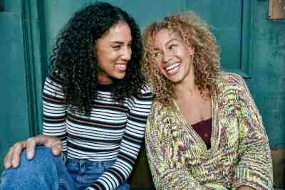 Portrait of two young smiling women with long curly black and blond hair, smiling and laughing.