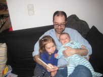 Brendan do an advanced Daddy move- reading with two on the lap.