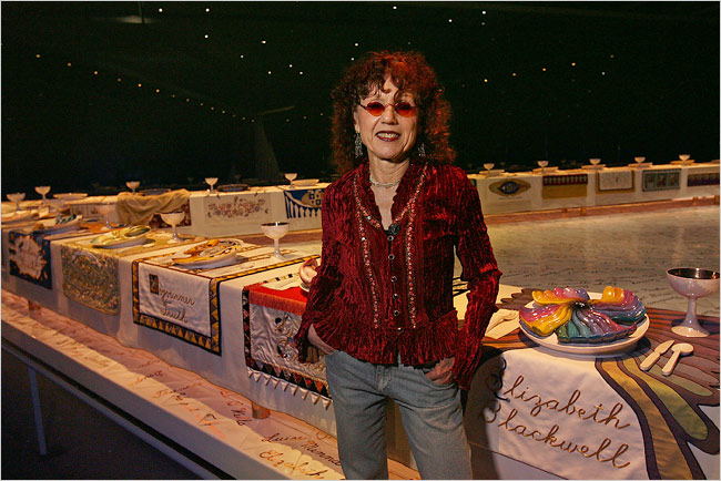 """The triangular shaped sculpture, conceptualized and designed by Judy Chicago, was created by hundreds of women volunteers in ceramic sculpture and woven, hand embroidered and sewn fabrics, all traditional """"craft"""" materials. The work is a permanent installation in the Brooklyn Museum's Elizabeth A. Sackler Center for Feminist Art"""