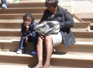 Symeir Talley-Jasper waits on the steps of City Hall with his grandmother during the press conference for the Audible Alarms Bill