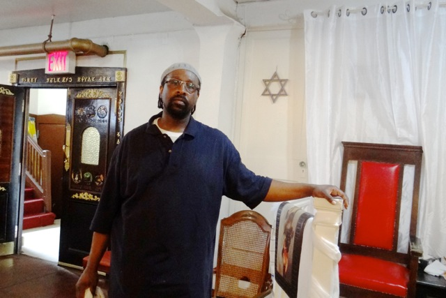 Rabbi Baruch Yehudah stands where his congregation worships in the basement level of his synagogue